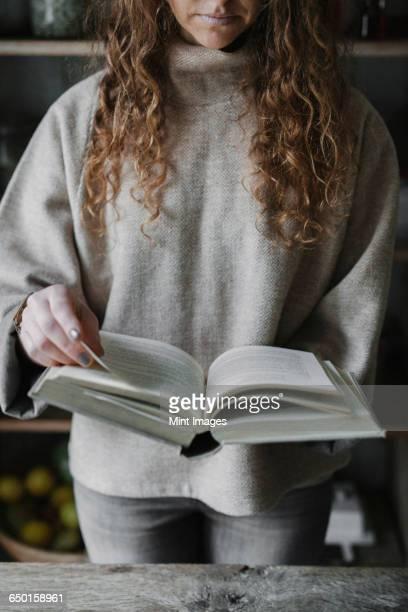a woman reading from a recipe book in a kitchen. - kochbuch stock-fotos und bilder
