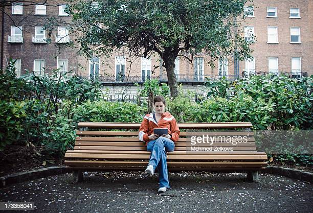 woman reading from her tablet in park - sitting stock pictures, royalty-free photos & images
