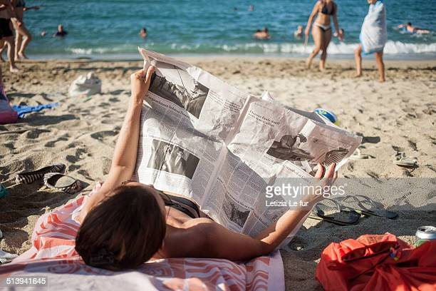 Woman reading geopolitics pages in a newspaper on a beach in Tinos Island Cyclades Greece