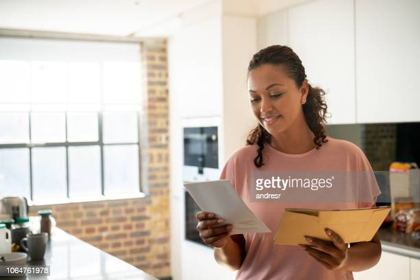 woman reading her mail at home - mail stock pictures, royalty-free photos & images