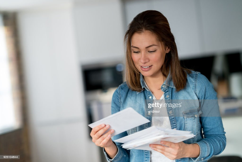 Woman reading her mail at home : Stock Photo