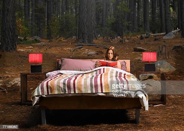 Une femme lisant sur un lit d'extérieur en bois
