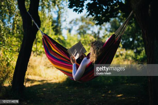 woman reading in a hammock. - hammock stock pictures, royalty-free photos & images