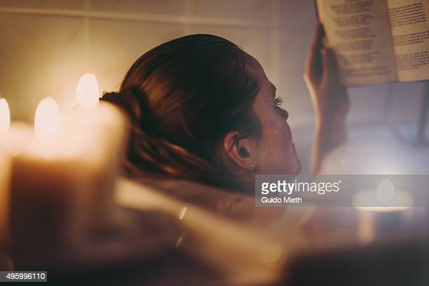 Woman reading in bathtub.