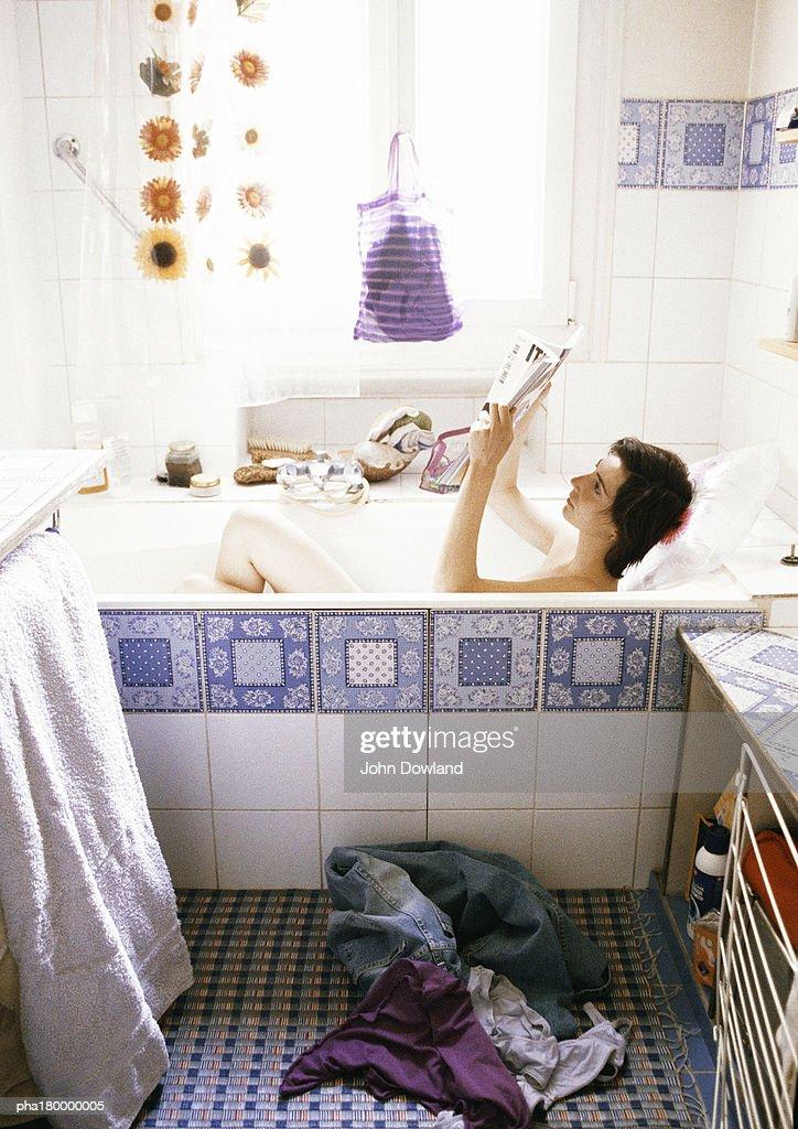 Woman reading in bathtub, side view : Stockfoto