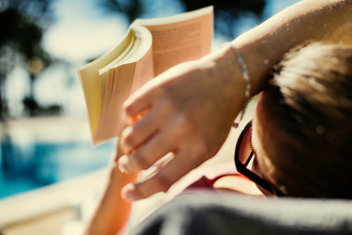 Woman reading in book in sunlight. - gettyimageskorea