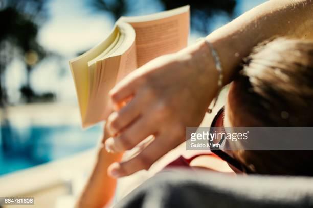 Woman reading in book in sunlight.