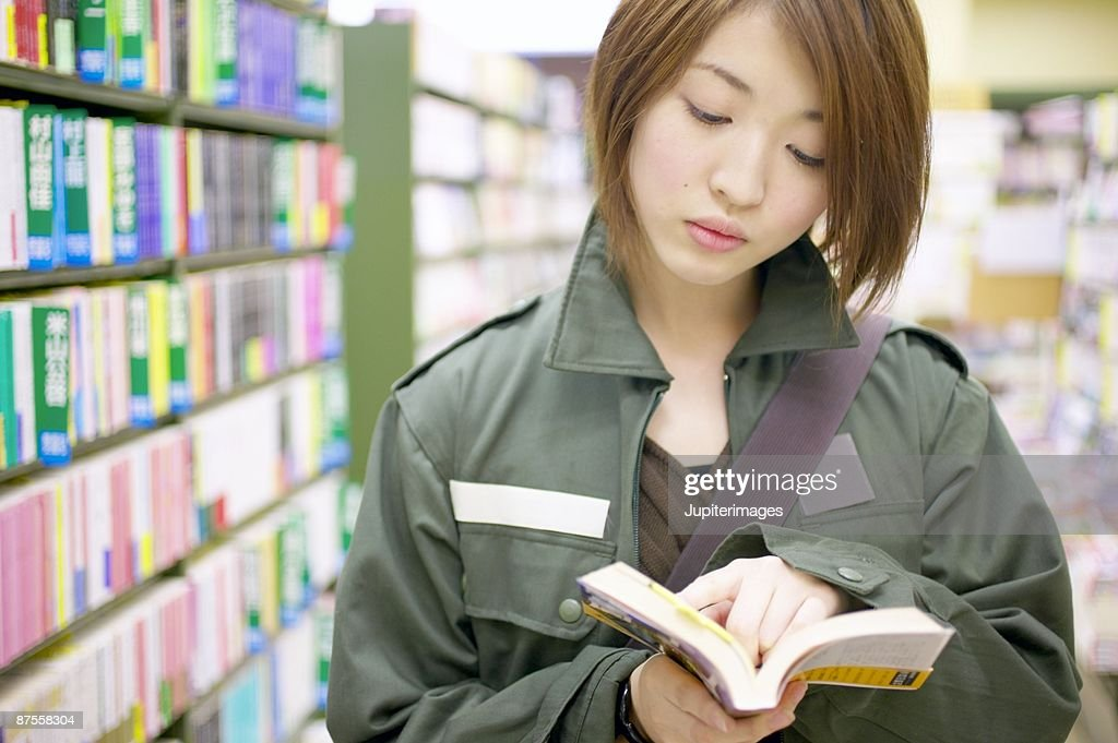 Woman reading in bookstore : Stock Photo