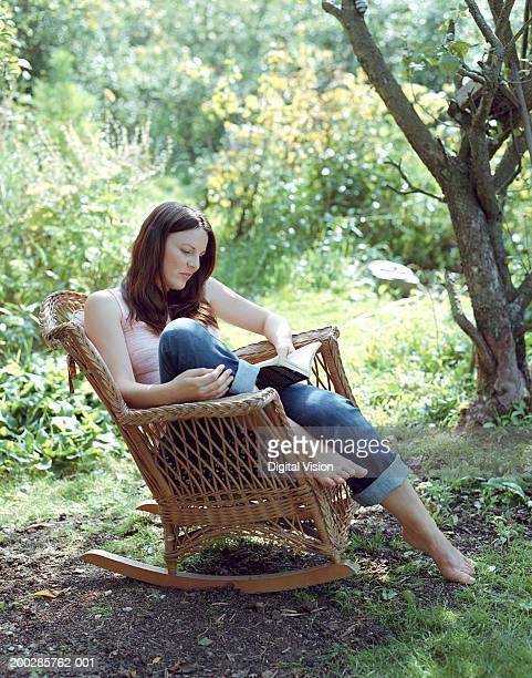 Woman reading in garden, sitting on wicker rocking chair