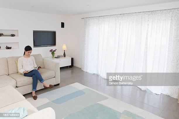 Woman reading in living room