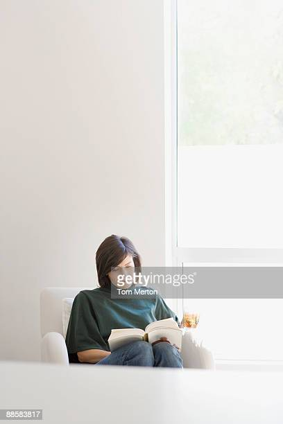 woman reading in living room - one mid adult woman only stock pictures, royalty-free photos & images