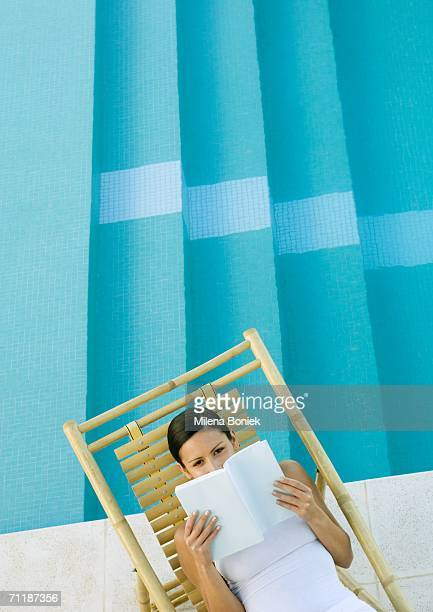 woman reading in lounge chair next to pool - chaise longue photos et images de collection
