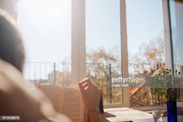 woman reading in sunlight. - lesen stock-fotos und bilder
