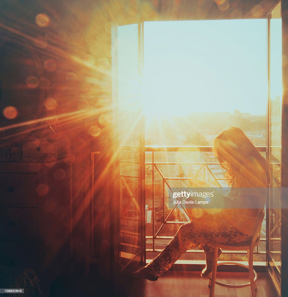 Woman reading in the morning sun : Stock Photo