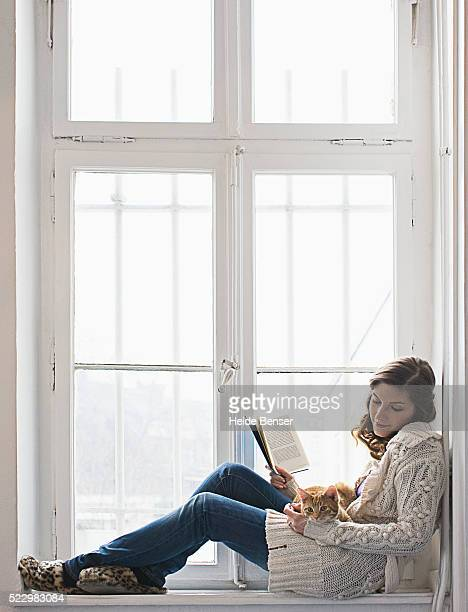 Woman reading in windowsill with cat in lap