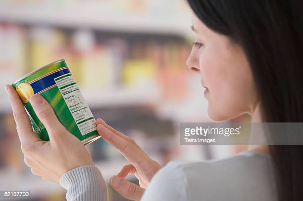 Woman reading label at grocery store