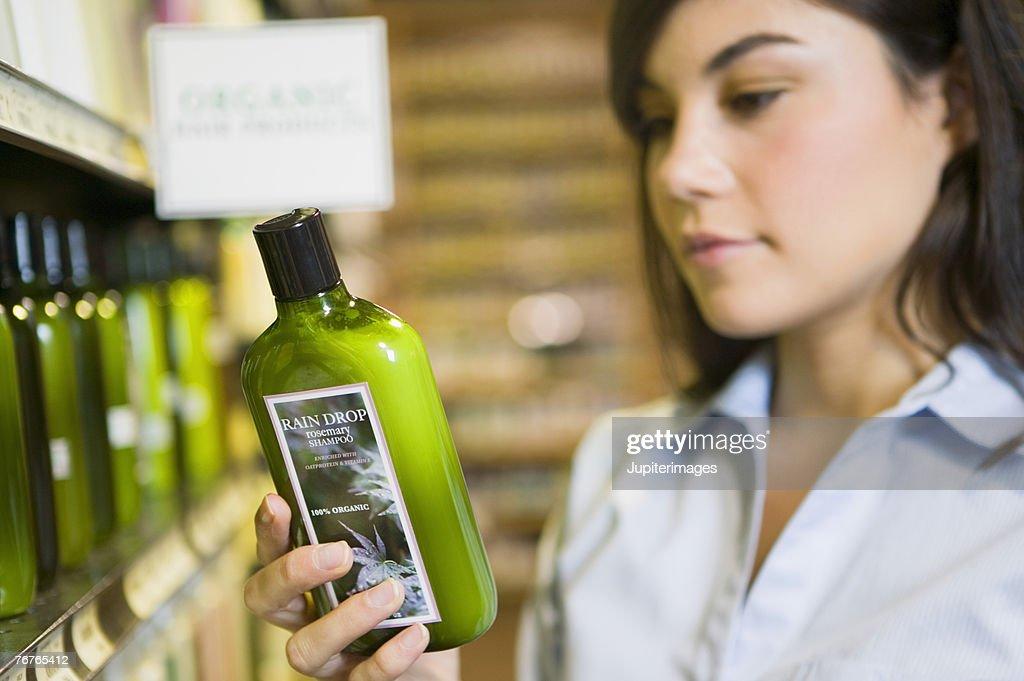 Woman reading label of organic shampoo : Stock Photo