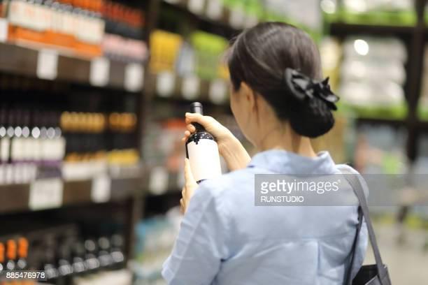 woman reading label on bottle in wine store - 後ろで束ねた髪 ストックフォトと画像