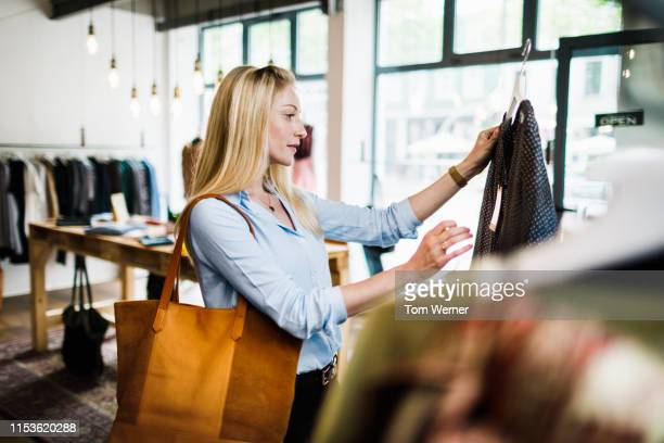 woman reading label on clothing while out shopping - winkelen stockfoto's en -beelden