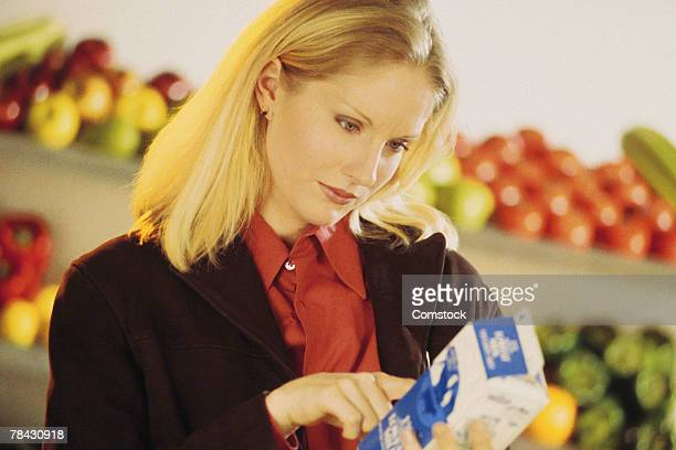 Woman reading label on milk carton