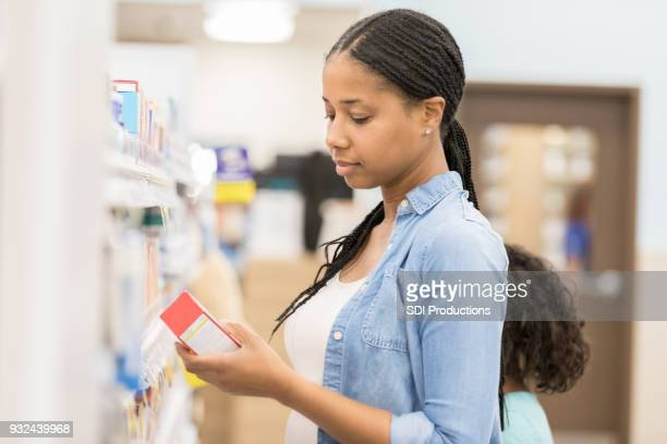 woman reading label on over the counter medication - pain relief stock pictures, royalty-free photos & images