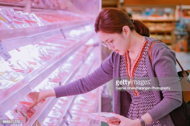 Woman reading label on the pack at supermarket