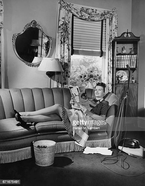 woman reading magazine and lying on sofa  - {{ collectponotification.cta }} foto e immagini stock