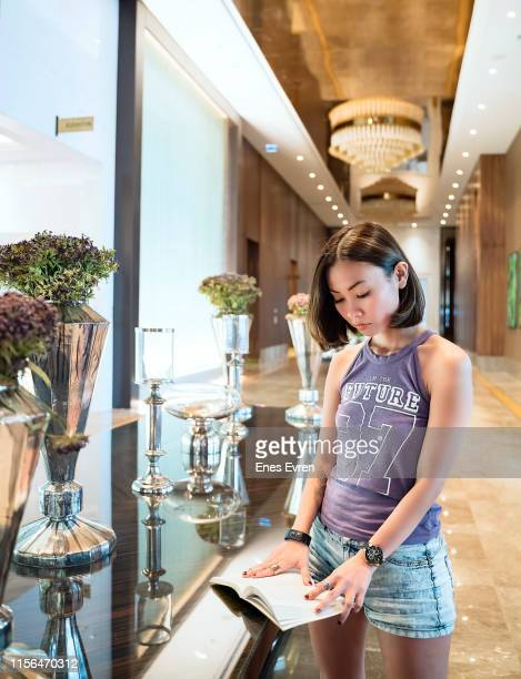 Woman reading magazine in luxury five stars hotel's lobby area