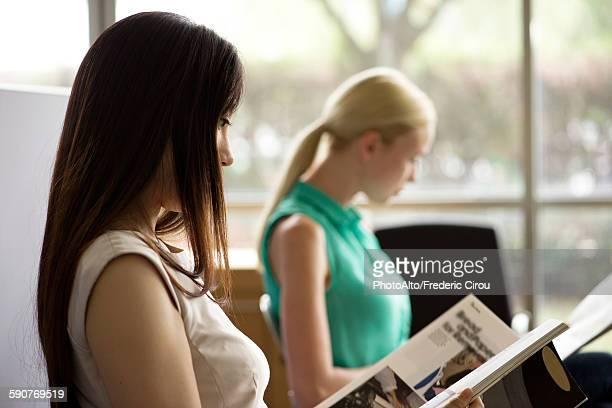 woman reading magazine in waiting room - treats magazine fotografías e imágenes de stock