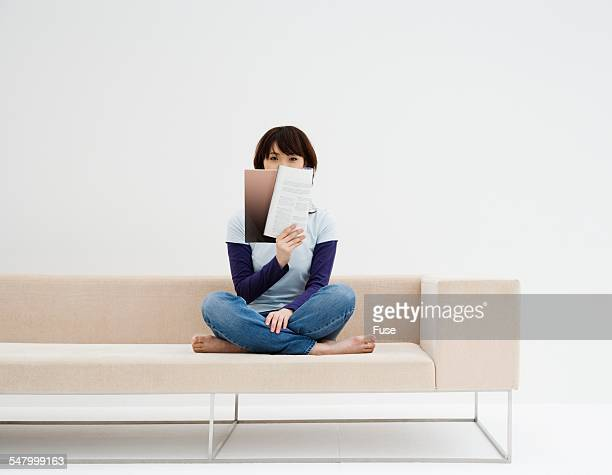 Woman Reading Magazine on Sofa
