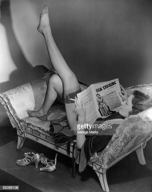 woman reading magazine - women wearing thigh high stockings stock photos and pictures
