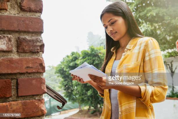 woman reading mail at mailbox - mail stock pictures, royalty-free photos & images