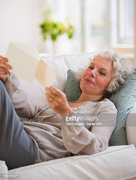 Woman reading mail while relaxing on couch