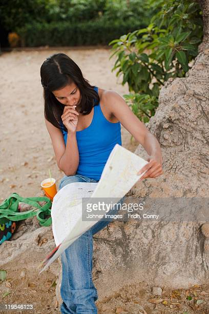 Woman reading map under tree in park