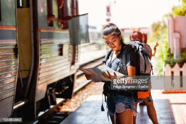woman reading map while standing at railroad station platform - rucksack stock pictures, royalty-free photos & images