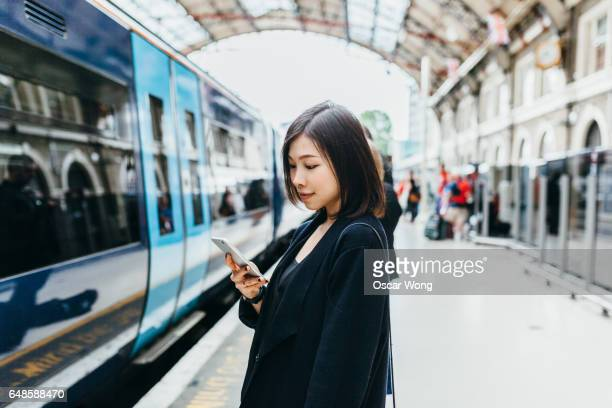 Woman reading message on phone in train station