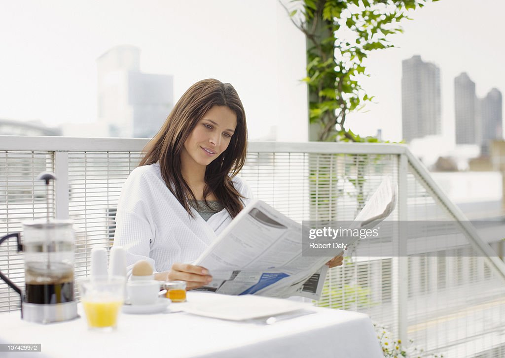 Woman reading newspaper and having breakfast on balcony : Stock Photo