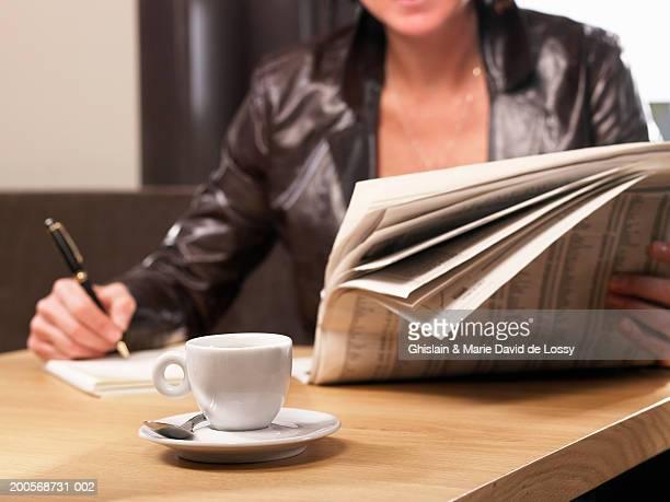 woman reading newspaper at restaurant, close-up, mid section - クラシファイド広告 ストックフォトと画像
