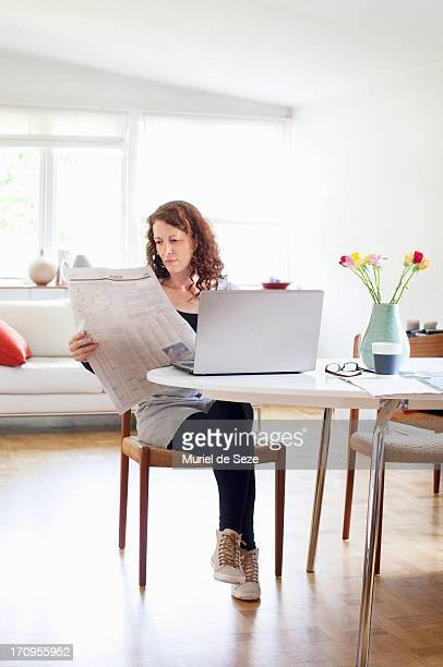 Woman reading newspaper by computer