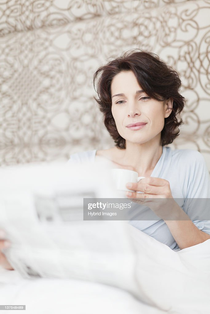 Woman reading newspaper in bed : Stock Photo
