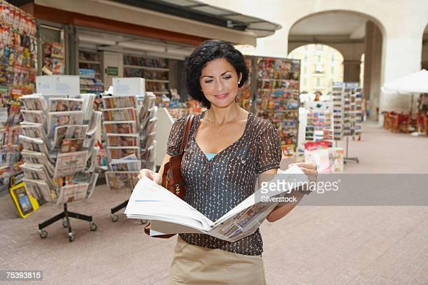 Woman reading newspaper in street