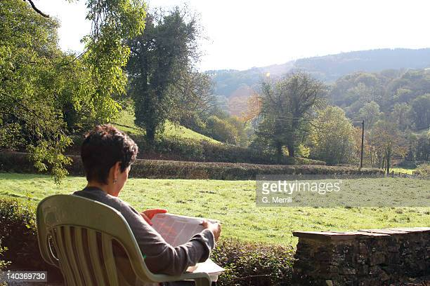 Woman reading newspaper on sunny day