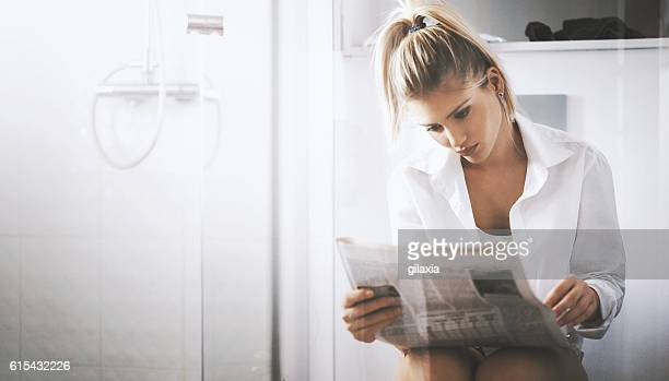 Woman reading newspapers while in toilet