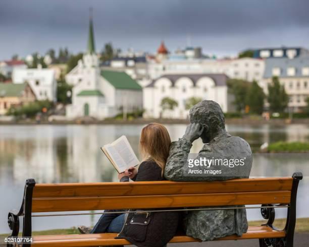 Woman reading next to statue of an Icelandic poet, Tomas Gudmundsson, Reykjavik, Iceland
