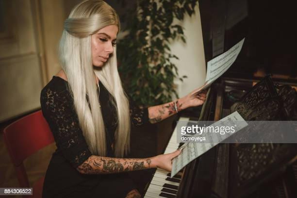 Woman reading notes and playing piano