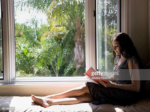 woman reading on a window bench - studio city stock pictures, royalty-free photos & images