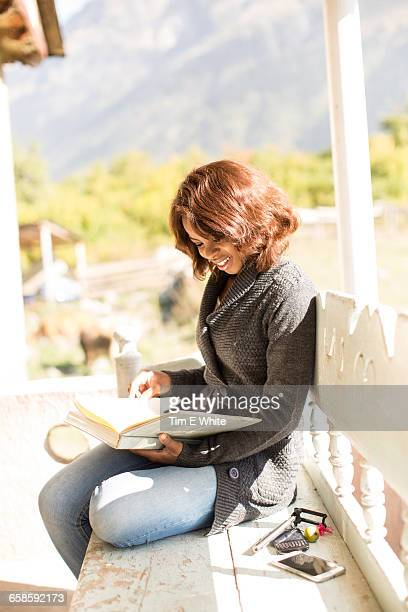 Woman reading on balcony, Ushba, Svaneti, Georgia