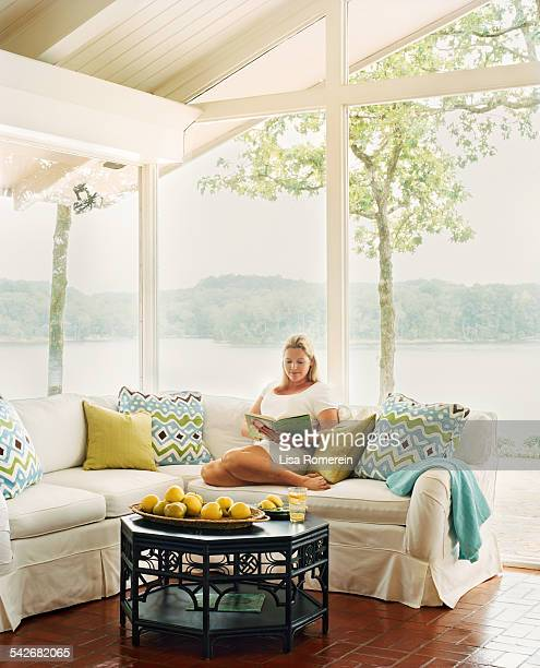 Woman reading on couch in room with view of lake