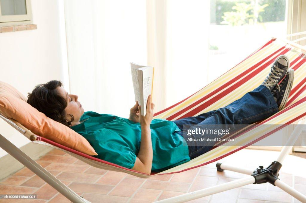 Woman reading on hammock in house : Foto stock