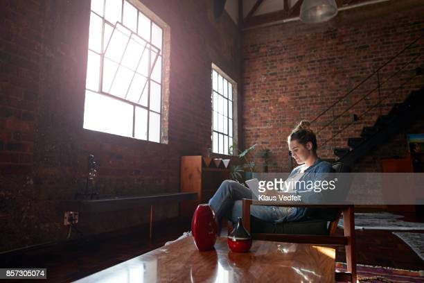 woman reading on tablet, in loft apartment - loft stock photos and pictures